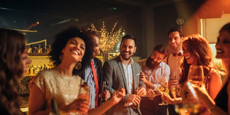 sober person at work holiday party surrounded by coworkers drinking
