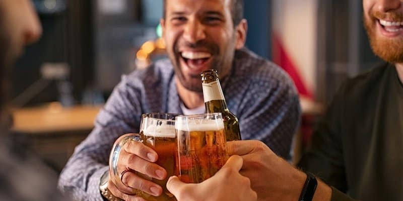 man with beer cheers his friends feels the happy effects of alcohol
