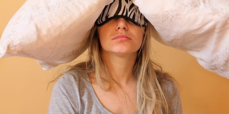 woman with pillow on head feeling the intense effects of alcohol the next day
