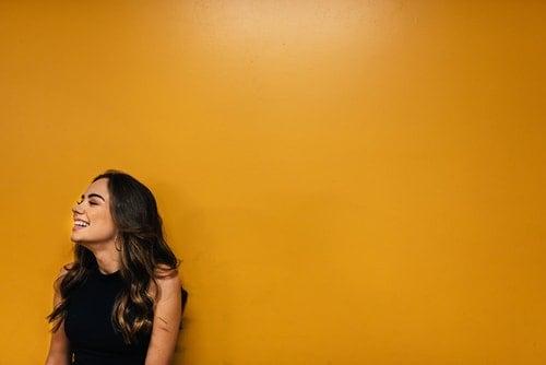 emotionally sober woman smiles against orange backdrop
