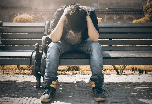 man struggling with emotions in sobriety sits on bench with hands in head