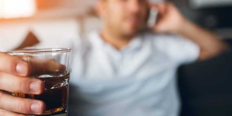 man with glass of alcohol about to relapse