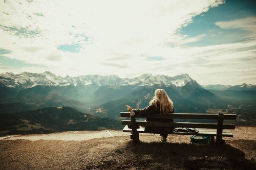 woman sits on bench and contemplates self forgiveness