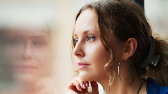 depressed woman looks out window