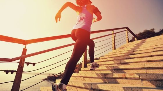 woman with healthy habits running up stairs