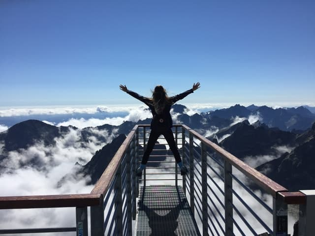 woman climbed a mountain excited about sobriety
