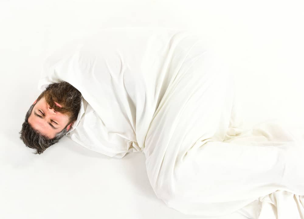 man sleeping under weighted blanket