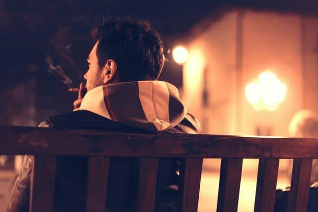 sober man smoking on a bench