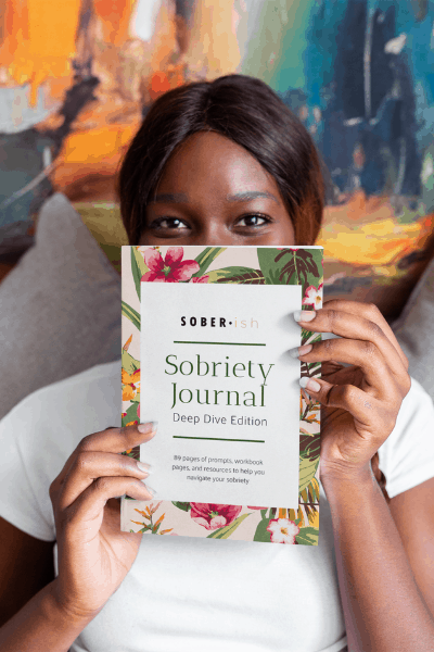 woman holding sobriety journal