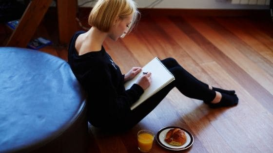 woman writing in her sobriety journal while eating breakfast
