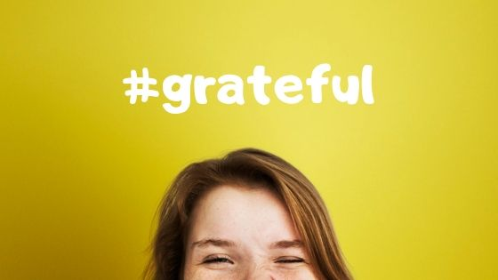 woman squints below sign that says hashtag grateful