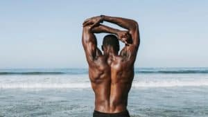 mentally strong man stretches by the ocean