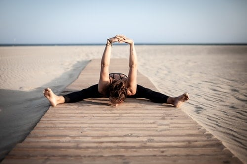 mentally fit woman stretches on the boardwalk