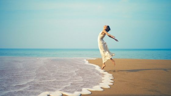 mentally strong woman jumps for joy at edge of shore
