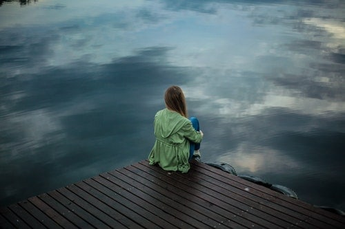 sad woman sits alone on a dock wondering when sobriety gets better