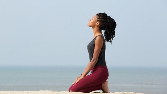 woman meditates on beach to battle cravings