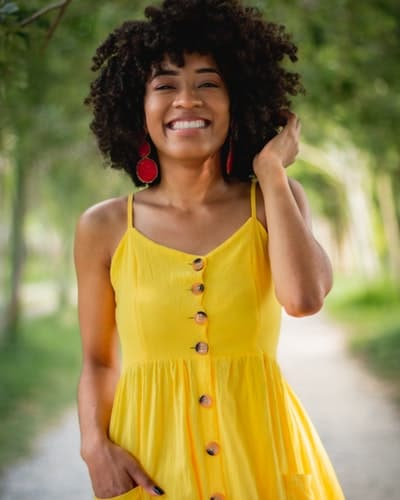 happy woman in yellow dress smiling because sobriety gets better