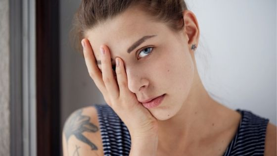 stressed woman with hand on face caught in craving cycle