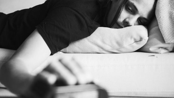 man lays down and checks clock wondering when sobriety gets better