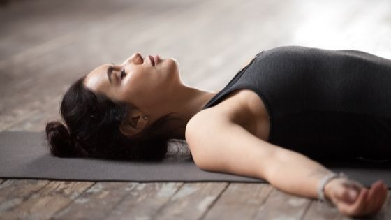 stressed woman lays down in shavasana