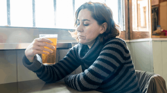 woman with a beer sitting down questioning her drinking
