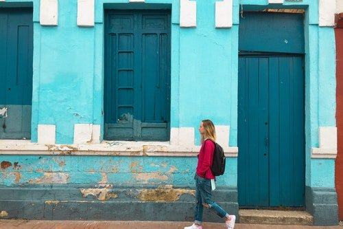 woman walking past blue wall