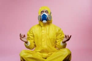 man in hazmat meditating