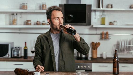 man drinking alone in kitchen