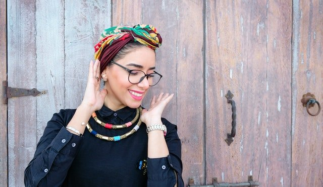 happy woman in colorful head wrap and glasses