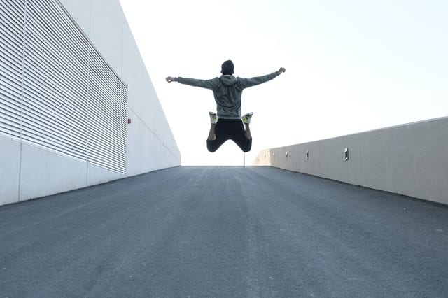 changed sober man jumping for joy on street